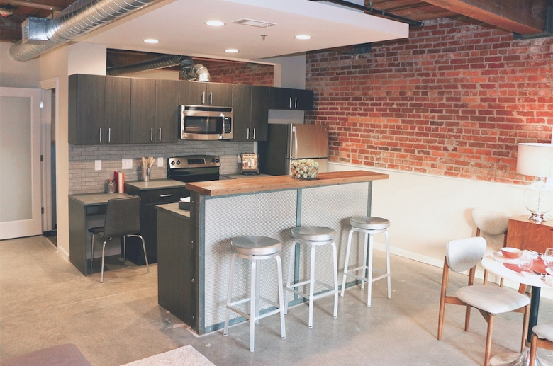 Palmetto Compress kitchen with granite countertops, breakfast bar, and stainless steel appliances
