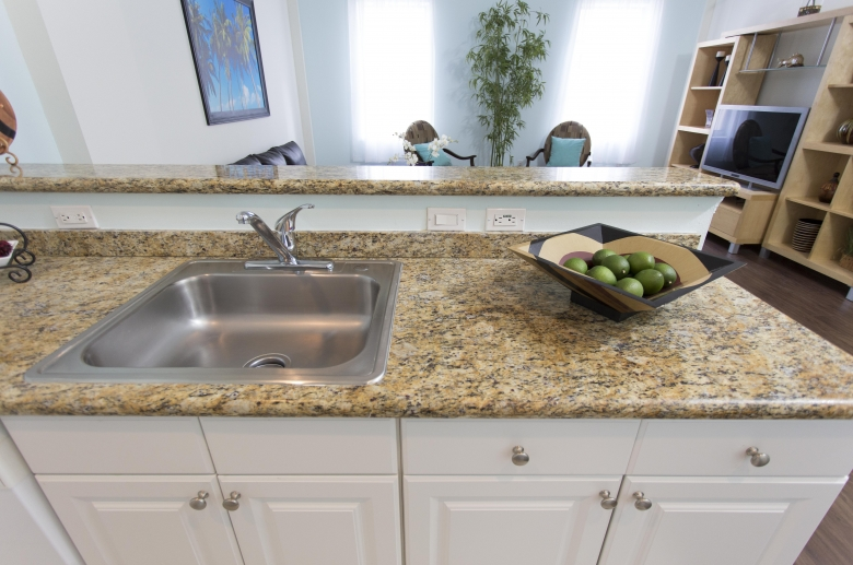 Breakfast bar features granite counter top and stainless steel under-mounted sinks