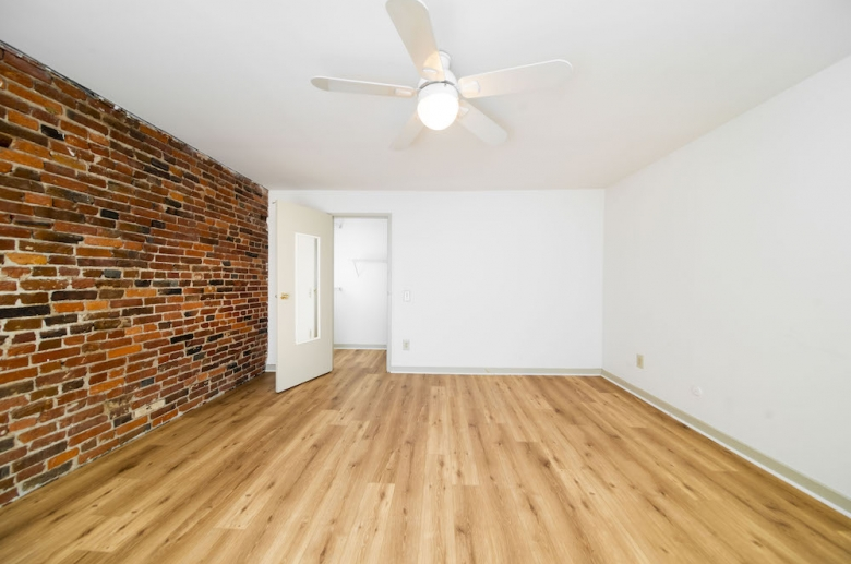 Bedroom featuring hardwood and exposed brick walls