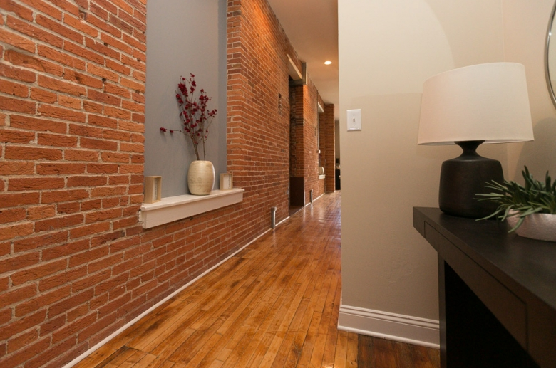 Hallway featuring brick wall and recessed lighting